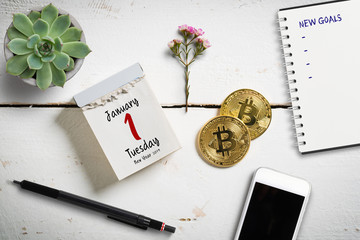 Tear-off calendar with 1st of January 2019 on top, surrounded by bitcoins and other decorative elements
