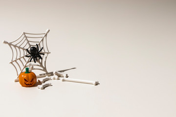 Composition of plastic toys for Halloween, with pumpkin, spider, cobweb, snake and bones