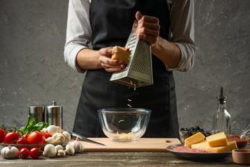 Rubbing mozzarella cheese chef cook for pasta, Italian pizza. The concept of food