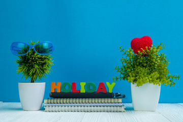 HOLIDAY letters text and notebook paper and little decoration tree in white vase on wooden background, hello weekend vacation concept.