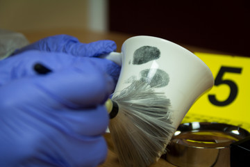 Forensic expert finds fingerprints on the cup of coffee. Crime scene