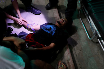 Paramedics treat a dehydrated Central American migrant, part of a caravan trying to reach the U.S., in Tecun Uman