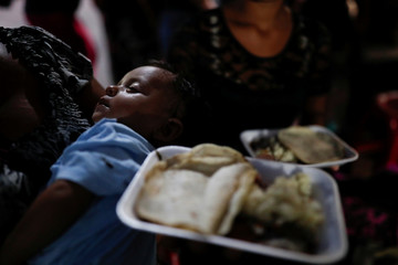 Eva Carrillo, migrant from Honduras, part of a caravan trying to reach the U.S., carries the baby of a friend after received a plate of food handed out at a church, in Tecun Uman