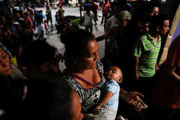 Eva Carrillo, migrant from Honduras, part of a caravan trying to reach the U.S., queues while carrying the baby of a friend, while she waits for food to be handed out at a church, in Tecun Uman