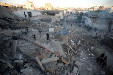 Palestinians inspect the scene of an Israeli air strike on a building in Gaza City
