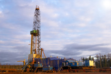 Oil and Gas Drilling Rig onshore dessert with dramatic cloudscape. Oil drilling rig operation on the oil platform in oil and gas industry.