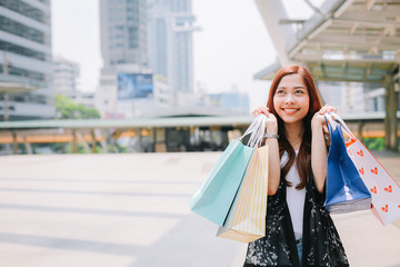 Beautiful woman holding a colorful shopping bag. She is happy and smiling while after shopping in the city.