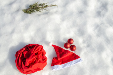 Traditional Christmas symbols on the snow. Santa's bag and hat, Christmas wreath and decorations for the Christmas tree