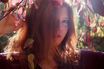 Portrait eines jungen reizenden fuchsigen Mädchens mit violettem Top, schöne sexy attraktive feurige Frau, Ginger, Rotschopf, unter violettem lila Herbst Busch,