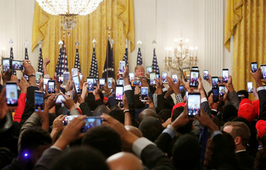 "Attendees take photos as U.S. President Trump hosts the ""2018 Young Black Leadership Summit"" in the East Room of the White House in Washington"