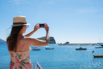 Young travelling woman in hat taking photos of summer sunny sea with smartphone camera. Brunette girl making photography on summer vacation