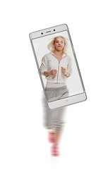 Portrait of young sporty woman running on white background. conceptual image with a smartphone, demonstration of device capabilities