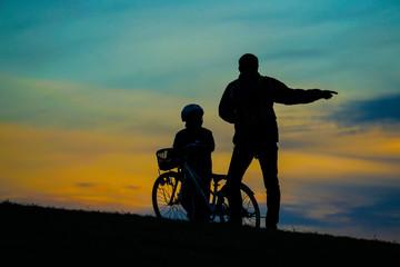 日没の丘に立つ親子のシルエット