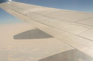 Picture of airplane wing, cloudy sky from porthole