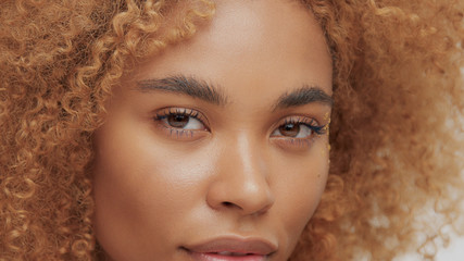 mixed race black blonde model with curly hair eyes closeup watching to the camera