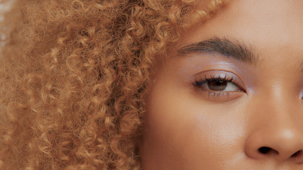 mixed race black blonde model with curly hair eye watching at camera closeup