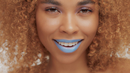 mixed race black blonde model with curly hair closeup of mouth painted with bright blue lipstick smiling and watching to the camera
