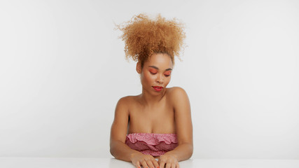 studio shot of mixed race woman sitting on the white table. Wears bright red makeup. Blonde curly hair