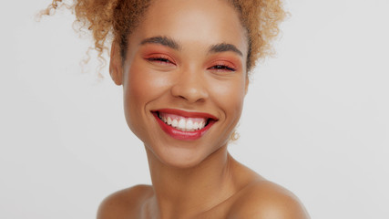 closeup portrait of mixed rase woman with red makeup in studio happy laughing smiling