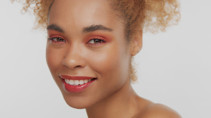 closeup portrait of mixed rase woman with red makeup in studio close up smiling and watching to the camera