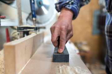 Carpenter sharpens a chisel in a small workshop, shallow depth of field.
