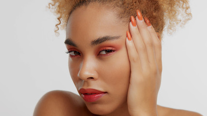 mixed race black blonde model with curly hair with bright red makeup with turned to the left face watching to the camera