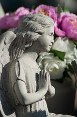 closeup of stoned angel praying at cemetery with purple flowers on background