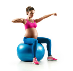 Pregnant woman exercising on fit ball isolated on white background. Concept of healthy life