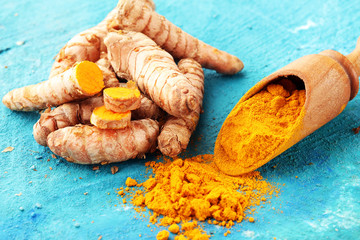 Turmeric powder and fresh turmeric on grey background
