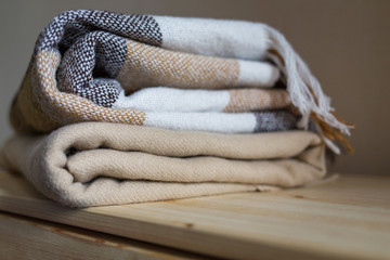 home textile. stack of beige wool blankets on a wooden shelf.