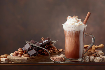 Fotobehang Chocolade Hot chocolate with cream, cinnamon, chocolate pieces and various spices.