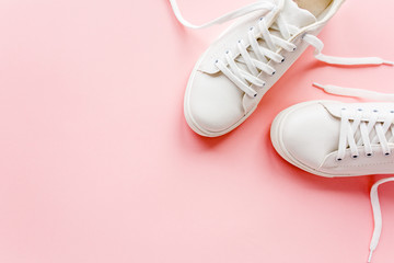 Wall Mural - White female sneakers on pink background. Flat lay, top view minimal background. Fashion blog or magazine concept.