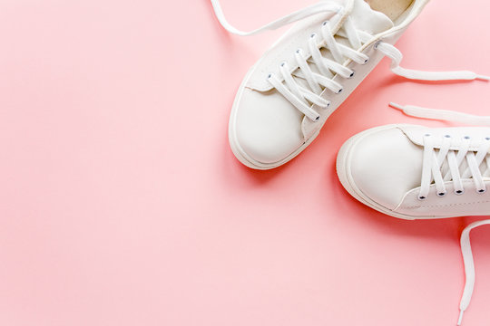 White female sneakers on pink background. Flat lay, top view minimal background. Fashion blog or magazine concept.