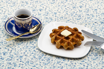 coffee and belgian waffle with butter on flower pattern tablecloth