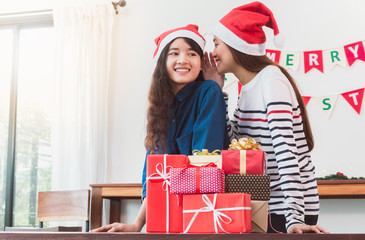 Asian woman whisper and give gift box to beautiful young Asian women.Smiling face in room with Christmas tree decoration for holiday background.Lover couple and celebration concept.