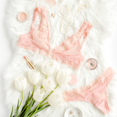 Flat lay set of sexy, lacy, pink lingerie, accessories on white background. Top view.