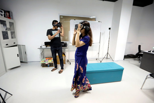 San Dar Nyunt Wai, Director of Operations at 360ed company, a Yangon based educational virtual and augmented reality company, demonstrates a VR headset at the company's office in Yangon