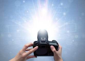 Naked hand taking picture with digital camera and glowing flash concept