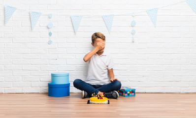 boy celebrating his birthday with a cake covering eyes by hands