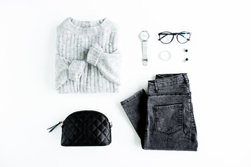 Women fashion clothes and accessories. Feminine youth collage on white background top view. Flat lay female style look with warm sweater, jeans, glasses. Top view.