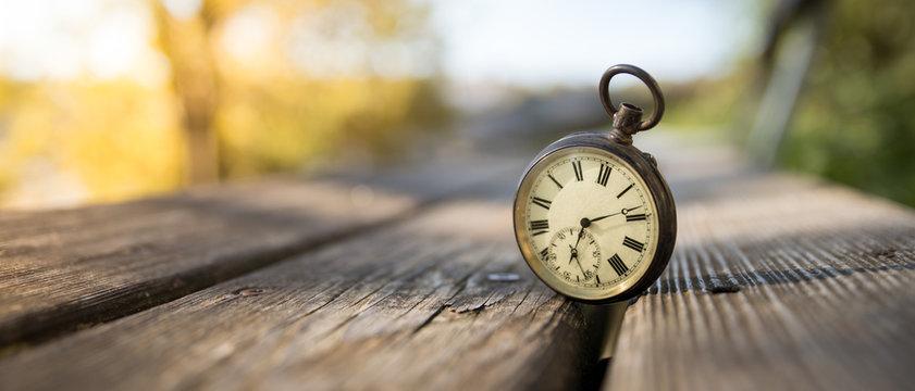 Retro Taschenuhr auf Holzbank, Himmel und bunte Blätter im Herbstlicht, Symbol für Zeit, Breitbild