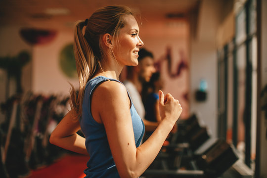 Young woman warming up on treadmill at gym