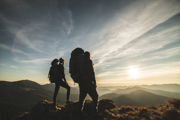 The couple standing on a mountain with a picturesque sunset background Wall mural