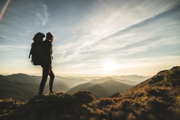 The woman with a camping backpack standing on a rock with a picturesque sunset