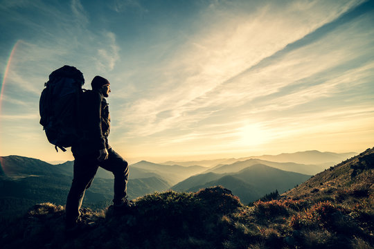 The man standing with a camping backpack on a rock with a picturesque sunset