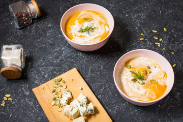 Thick pumpkin soup with feta cheese on stone background.