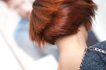 Accurate geometric shape short haircut on a woman with red hair in detail