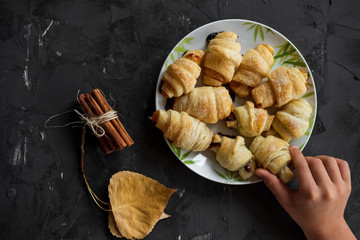 Kid hand with Small homemade croissants on a black background