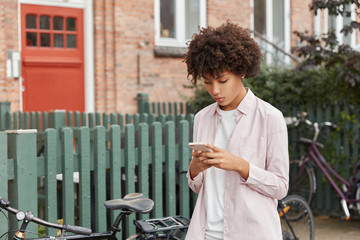Hipster bloger with Afro haircut watches video in social networks, reads news on website, has outdoor stroll near fence, bikes, brick building, wears casual loose shirt, connected to wireless internet