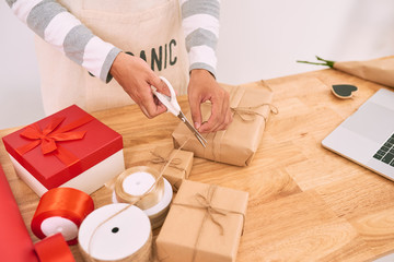Asian man wrapping purchase while working in shop of gifts.